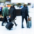 People with baggage on the move at an airport, shown in motion blur — Stock Photo #56663439