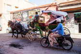 Typical street scene in Marrakech, Morocco, with a moped rider and a carriage rider — Stock Photo