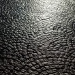 Background texture from dark cobblestone pavement with light spot — Stock Photo #58983783