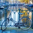 Bicycle leaning at a handrail of a canal bridge in Amsterdam, Netherlands — Stock Photo #58984477