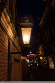 Dark alley with street lighting in the old town of Amsterdam, Netherlands, at night — Stock Photo