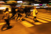 People crossing a city street at night in motion blur — Stock Photo