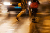 People in motion blur crossing a street at night in the backlight of car headlights — Stock Photo