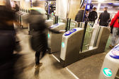 People in motion blur at a turnstile of a metro station — Stock Photo