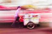 Thai woman with a mobile cook shop on a handcart, shown in creative motion blur — Stock Photo