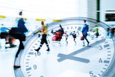 Multi exposure picture with time concept of traveling people in motion blur at an airport with a clock face — Stock Photo