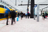 Traveling people in motion blur at a railway station — Stock Photo