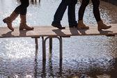 Walking legs on a footbridge at flood in Venice — Stock Photo