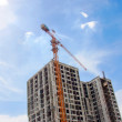 Close up building and cranes under construction against blue sky — Stock Photo #55409921