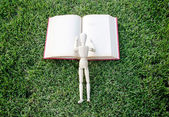 Close up wood model reading vintage book on park — Stock Photo