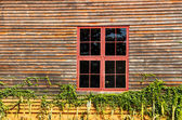 Red metal windows on wood wall — Stock Photo