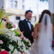 Just married couple being happy after wedding ceremony in a Roman catholic church with a beautiful set of flowers — Stock Photo #58094929