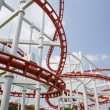 Red roller coasters in amusement park or theme park look fun and  attract large numbers of people to ride and enjoy  its fast and steep drops from high altitudes and inversions which turn upside down — Stock Photo #58095683