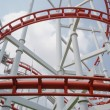 Red roller coasters in amusement park or theme park look fun and attract large numbers of people to ride and enjoy its fast and steep drops from high altitudes and inversions which turn upside down — Stock Photo #58095785