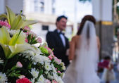 Just married couple being happy after wedding ceremony in a Roman catholic church with a beautiful set of flowers — Stock Photo