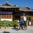 Cyclist cycles past old traditional Korean houses in Keonju Hanok Village, South Korea. — Stock Photo #58158573