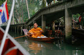 Buddhist monk in a canoe — Stock Photo