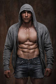 Young muscular man with open jacket revealing muscular chest and abs. — Stock Photo
