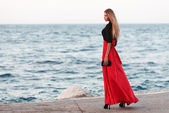 Sexy young beauty woman in fluttering red dress at the coast. Fashion woman — Stock Photo