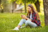 Attractive smiling girl typing on cell phone in summer city park. Modern happy woman with a smartphone, outdoor — Stock Photo