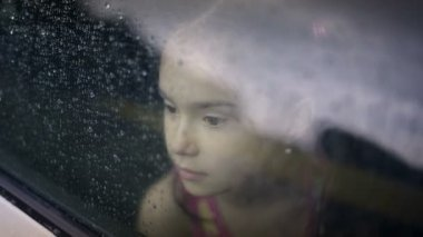 Child female in the car in raining — Vídeo stock