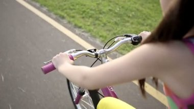 Little girl cycling in park on a pink bike. Slow motion — Stock Video