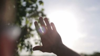 Sun's rays through fingers palm. Male. Slow motion — Стоковое видео