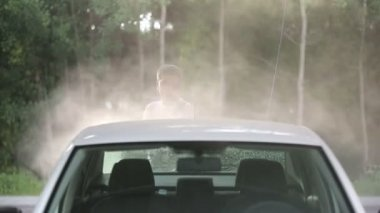 Man in a white t-shirt white car washes. — Wideo stockowe