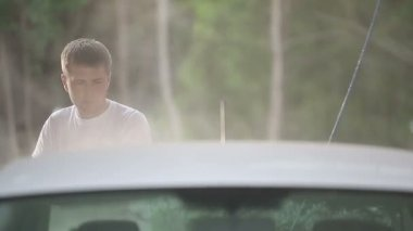 Man in a white t-shirt white car washes. — Stock Video