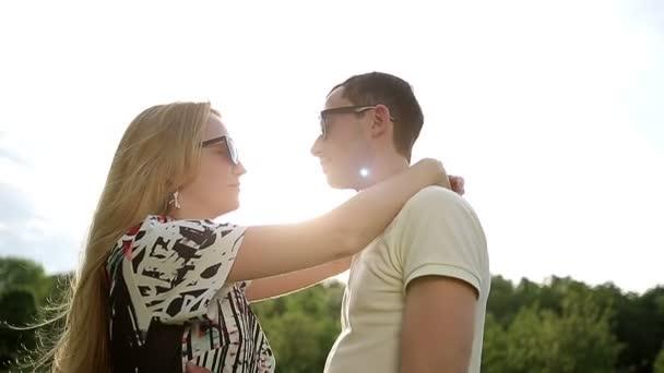 Pareja amorosa en gafas de sol en puesta de sol lenta — Vídeo de stock