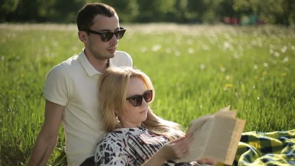Loving couple in sunglasses at sunset read book on field with dandelions — Vidéo