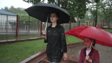 Mother and daughter walking on the street in heavy rain. — Stock Video