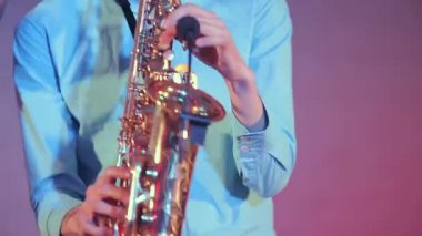 Saxophone player performs on stage with professional light. Close up. — Stock Video