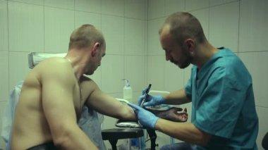 Tattoo artist working. Man draws on his arm woman's face. Tattoo salon — ストックビデオ