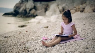 A child sits on a stone near the Adriatic Sea and draws a picture. — Stock Video