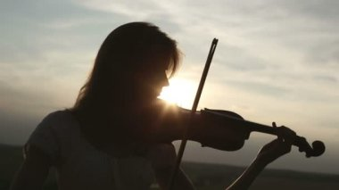 Silhouette girl violinist playing the violin at sunset sky background. Long shot. Color v.2 — Stock Video