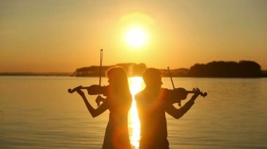 Violin duet man and woman play violin on nature at the sunset on the lake — Stock Video