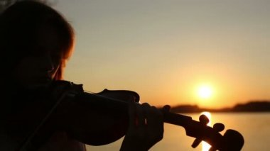 Female violinist playing the violin at the lake at sunset — Stock Video