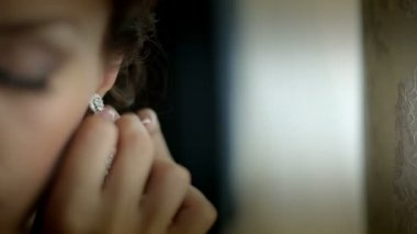 The young woman puts on beautiful earrings — Stock Video