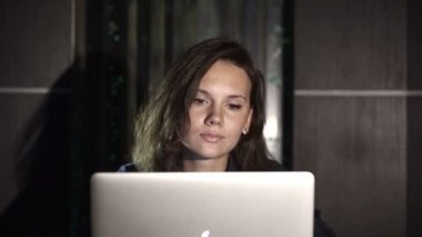 Girl working on computer in the evening in the interior with water background which symbolizes the flow of ideas. — Stock Video