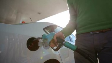 A man fills a white car quality biofuels at sunrise — Vídeo de Stock