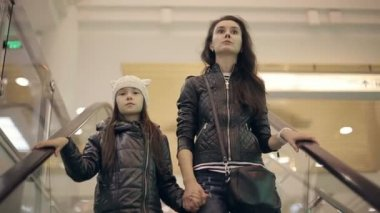 Mother and daughter in a supermarket on the escalator. — 图库视频影像