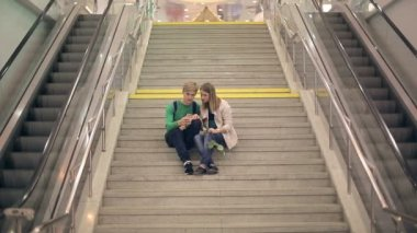 Young loving couple take selfie sitting on the steps of the college — Stock Video