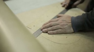The man working at the factory. Cuts cardboard frame for making handbags. — ストックビデオ