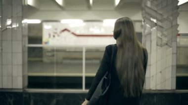 Girl teenager waiting for the subway train waits and comes aboard — Video Stock