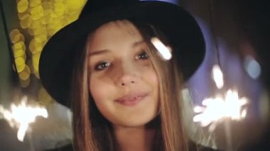 SLOW MOTION: Portrait of a girl model looks with sparklers in their hands — Vídeo de stock