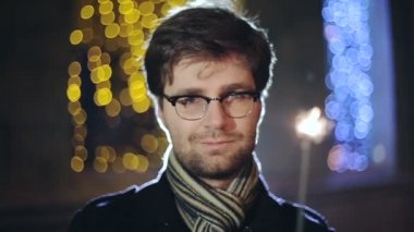 SLOW MOTION: Portrait of man with a sparkler in hand bokeh background — Vídeo de stock