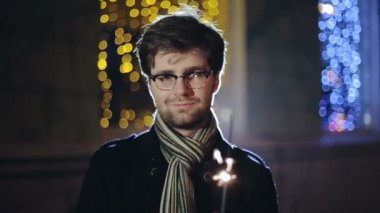 Man with a sparkler in hand bokeh background. — Vídeo de stock