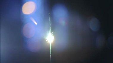 Sparkler burns at blue bokeh background — Vídeo de stock