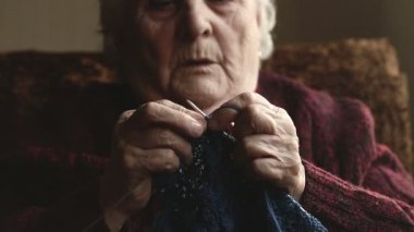 The old woman sits at home and knits garments — Video Stock